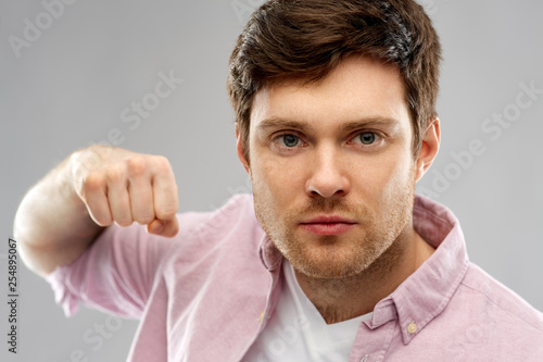 Leinwanddruck Bild violence, aggression and people concept - angry young man ready for fists punch over grey background