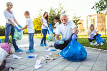 "Постер, картина, фотообои ""Volunteers with garbage bags cleaning up garbage outdoors - ecology concept."""