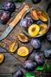 Ripe plum in glass bowl on cutting Board with knife.