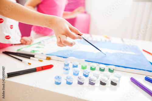 little artist hands with brush painting on canvas