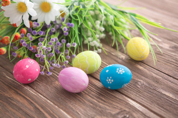 Colorful Easter eggs and spring flowers on rustic wooden background.