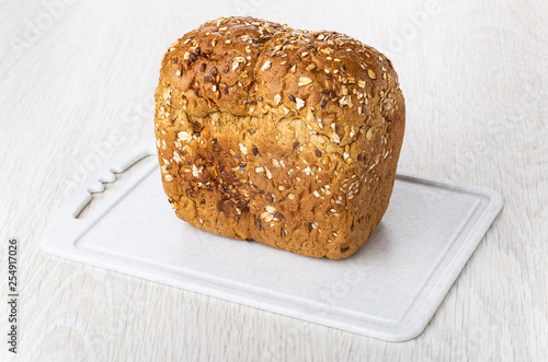 Loaf of bread with flax seeds, sunflower seeds, pumpkin seeds, rye bran, oat flakes on cutting board on table