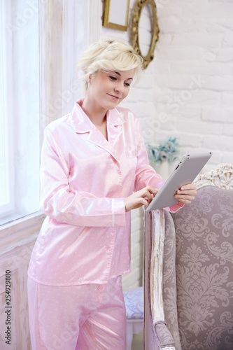 Woman in pajamas using tablet at home