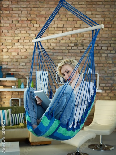 Woman sitting in hanging chair using tablet