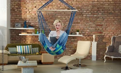 Blonde woman relaxing in hammock like chair