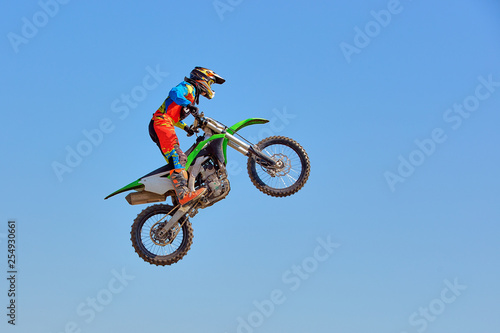 Extreme sports background - silhouette of biker jumping on motorbike on sunset, against the blue sky