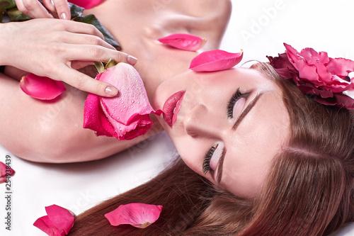 Leinwanddruck Bild beautiful young woman on rose petals background.