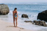 Backside view girl walks on beach with bottle of cool water in her hands