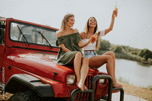 Leinwanddruck Bild Attractive young women sitting on a convertible car by river
