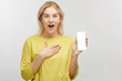Shocked European blonde woman with mobile phone in hand, eyes bulging in surprise, emotions from what she sees on screen and keeps jaw dropped. Portrait of a beautiful girl isolated in white studio