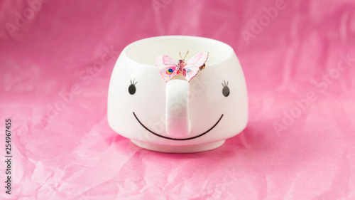 On a pink background with white Cup and pink butterfly - 254967455
