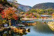KYOTO, JAPAN - NOVEMBER 26, 2018: Boatman punting the boat for tourists to enjoy the autumn view along the bank of Hozu river in Arashiyama Kyoto, Japan