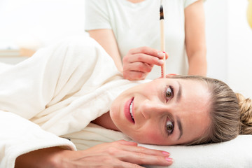 Woman's head with burning ear candle