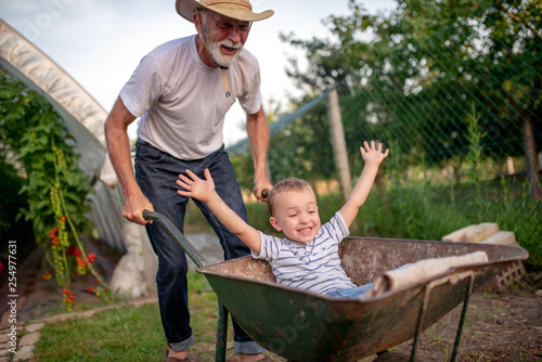 Grandfather and his grandson enjoy in garden © ivanko80
