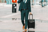 Businessman in formal wear pulling luggage and walking on the street. Business trip concept.