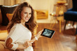 happy woman watching video from security camera on tablet PC