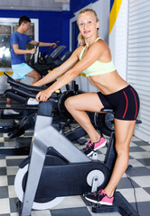 Fitness woman doing cardio workout cycling bike at gym