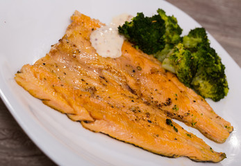 Deliciously steak of  fried rainbow trout fillet with broccoli on plate