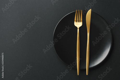 Gold cutlery set on black background - 254988875
