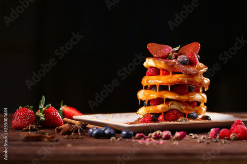 Multilayer berry pancake on a plate on a black background. Still life concept. © Alla