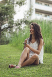 young woman sitting on the grass listening to the music on the phone