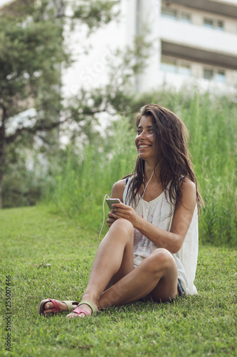 young woman sitting on the grass listening to the music on the phone - 255007446