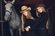 Girls with a horse. Women in a ranch. Blonde in a black sweater