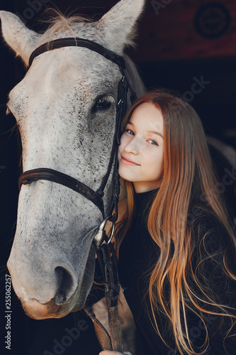 Leinwanddruck Bild Girl with a horse. Woman in a ranch. Blonde in a black sweater
