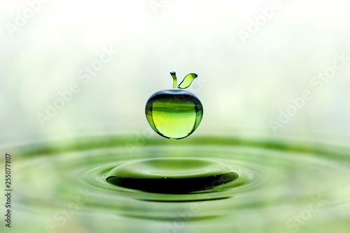 Falling water drop in green apple shape - 255077807