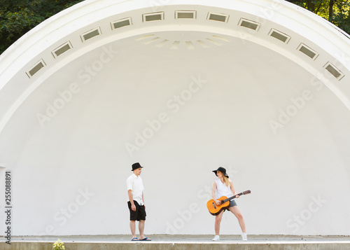 Woman playing guitar, man jumping next to her