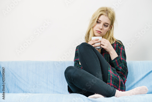 Sad lonely woman sitting on couch with mug © Voyagerix