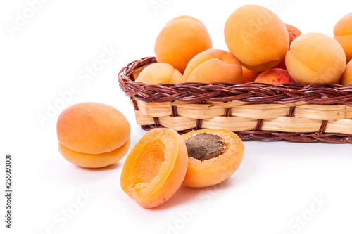 Several of harvested apricots in basket with whole and halved apricots on white background.. - 255093001