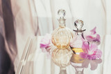 Spa still life with perfume and aromatic oils bottles surrounded by flowers