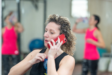 Business woman at the gym speaking at the phone. Other woman drinking on the background. Fitness and business concept