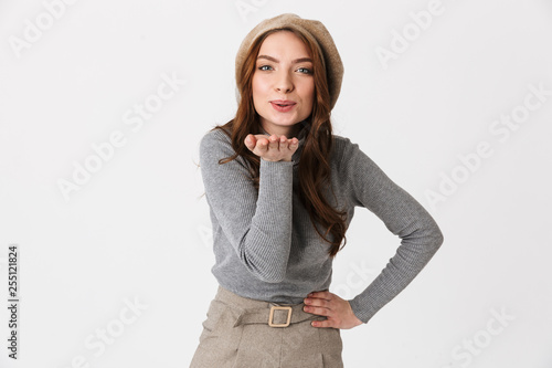 Cheerful young woman standing isolated