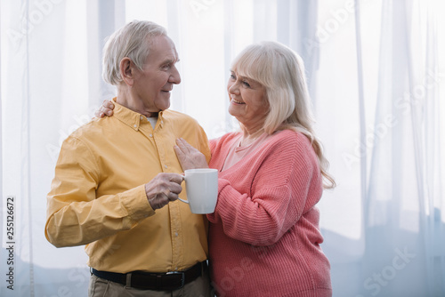 smiling senior woman with grey hair looking at camera and embracing man with cup of tea at home