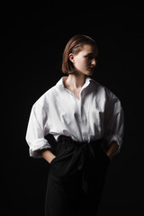 Portrait of an elegant young woman in a white shirt and black pants. Interesting studio light