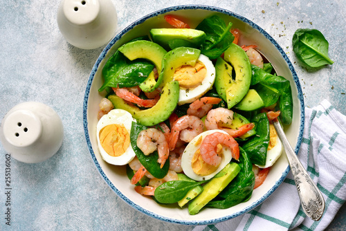 Leinwandbild Motiv Avocado salad with baby spinach, shrimps and boiled eggs.Top view with copy space.