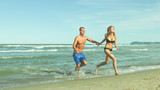 young couple running on beach hand in hand, romantic honeymoon vacation active holiday concept
