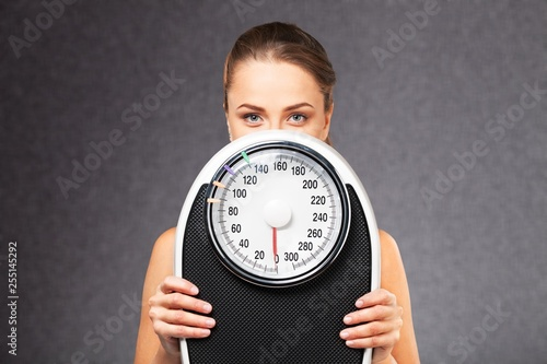 Leinwandbild Motiv Young woman hiding by scales on grey