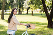 cheerful pretty girl smiling while riding bicycle in park