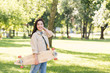 cheerful pretty girl smiling while holding longboard in park