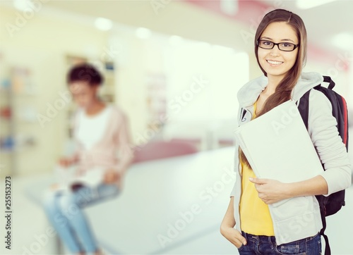 Young smiling woman holding blue notebook