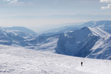 Silhouette of skier on snowy off-piste slope and mountains in haze