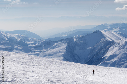 Leinwanddruck Bild Silhouette of skier on snowy off-piste slope and mountains in haze