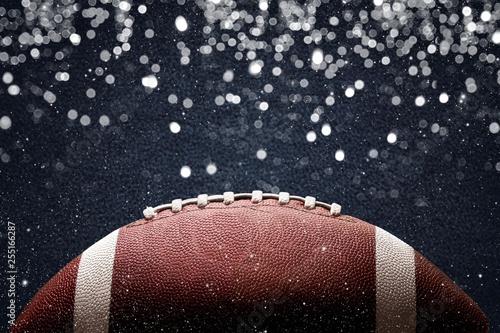Leinwanddruck Bild American football ball on black background illuminated by the light
