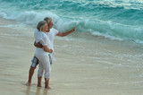 Elderly couple rest at tropical beach, man pointing by his hand