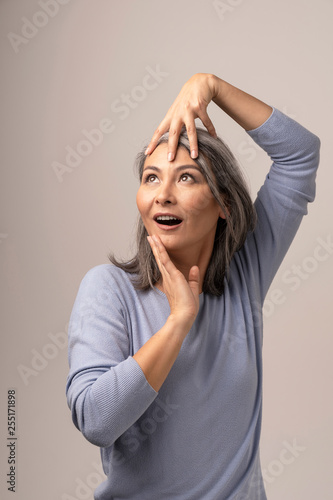 Attractive Asian woman is emotionally posing touching her head with hands