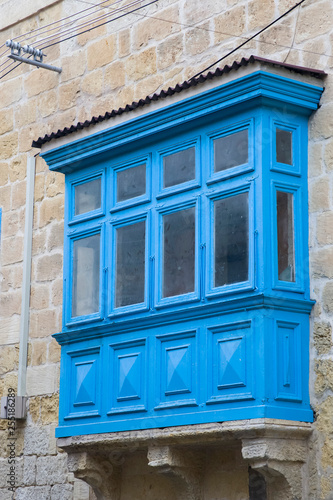 Traditional, wooden balcony and stone facade, typical for architecture of Gozo, Malta - 255186289
