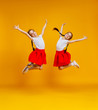 Quadro funny children girls twins jumping on colored yellow background.